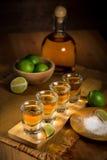 I colpi di tequila raggruppati insieme ad una bottiglia ed alle calce tagliate su un ristorante escludono la tavola Fotografia Stock