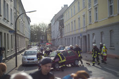 I combattenti di fuoco provano a mettere fuori un'automobile ed a liberare la zona dopo una o Immagine Stock