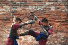 I combattenti partecipano ad una recinzione tailandese antica all'aperto Immagini Stock