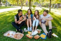 I compagni dell'istituto universitario stanno mangiando all'aperto fotografia stock