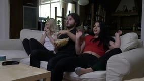 I compagni di camera che mangiano il popcorn ottengono spaventati mentre guardano il film horror video d archivio