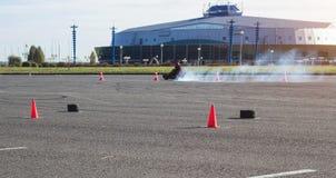 I concorsi di Karting, driver karting determina un kart contro lo sfondo di una costruzione moderna, molto fumo, il vincitore, av immagine stock libera da diritti