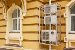 I condizionatori d'aria sulla via appendono sulla parete della casa nella griglia, proteggente li dai ladri immagini stock libere da diritti