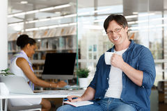 I am confident I can achieve the best results. Confident young businessman with his collegue in the background Royalty Free Stock Photo