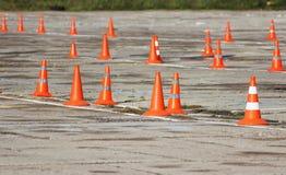 i coni di plastica di traffico di segnalazione stanno stando sul sito in cui i driver passano all'esame l'azionamento dei camion  Fotografia Stock