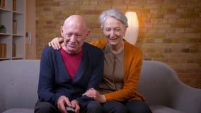 I coniugi caucasici senior guardano la commedia sulla TV che si abbraccia che ? allegro e rilassato al sof? in salone stock footage
