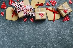 I contenitori di regalo con i cuori ed il cuore rossi decorativi hanno modellato i biscotti Fotografia Stock