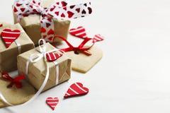 I contenitori di regalo con i cuori ed il cuore rossi decorativi hanno modellato i biscotti Fotografie Stock