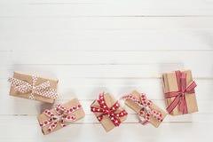 I contenitori di regalo con i nastri rossi su un bianco hanno dipinto il fondo di legno Fotografie Stock