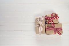 I contenitori di regalo con i nastri rossi su un bianco hanno dipinto il fondo di legno Fotografia Stock