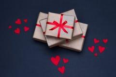 I contenitori di regalo decorati con i nastri rossi con gli archi si trovano su un fondo nero Fotografie Stock Libere da Diritti