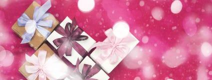 I contenitori di regalo dell'insegna legati con raso hanno colorato il nastro su un fondo rosa un cuore rosso Fotografia Stock Libera da Diritti
