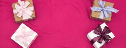I contenitori di regalo dell'insegna quattro legati con raso hanno colorato il nastro su un fondo rosa un cuore rosso Immagine Stock