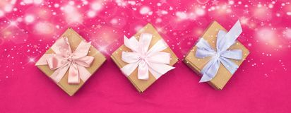 I contenitori di regalo dell'insegna tre legati con raso hanno colorato il nastro su un fondo rosa un cuore rosso Fotografia Stock Libera da Diritti