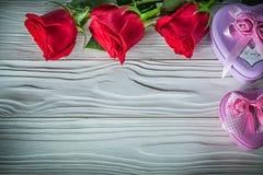I contenitori di regalo in forma di cuore del metallo hanno fiorito rose rosse sul bordo di legno Fotografia Stock