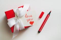 """I contenitori di regalo rossi legati con un nastro bianco, un indicatore e una carta con un'iscrizione """"vi amano """"su un fondo leg fotografia stock libera da diritti"""