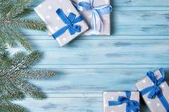 I contenitori e l'abete di regalo di Natale si ramificano con neve, il fondo di legno, vista superiore Immagine Stock Libera da Diritti