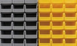 I contenitori grigi e gialli di plastica sono impilati in parecchie file immagini stock libere da diritti