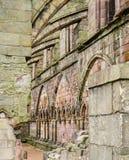 I contrafforti di volo sostengono una bella parete di pietra medievale di una rovina della chiesa fotografie stock