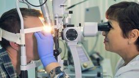 I controlli femminili di un oftalmologo giovane gli occhi con una lampada a fessura in una clinica 4K video d archivio