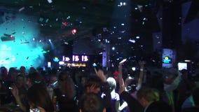 I coriandoli cadono sulla gente di dancing sul partito in night-club Fascio variopinto dai riflettori intrattenimento stock footage