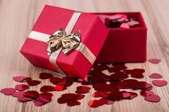 I coriandoli rossi dei cuori nel biglietto di S. Valentino della scatola amano il concetto Immagine Stock