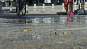 I corridori femminili hanno passato le pozze dell'acqua che spruzzano sotto le scarpe da corsa stock footage