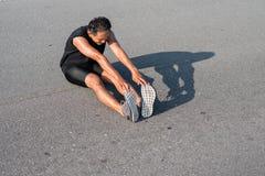 I corridori maschii stanno allungando i muscoli della gamba per preparare per un funzionamento Fotografie Stock Libere da Diritti