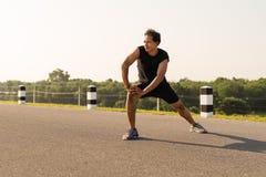 I corridori maschii stanno allungando i muscoli della gamba per preparare per un funzionamento Immagini Stock