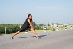I corridori maschii stanno allungando i muscoli della gamba per preparare per un funzionamento Fotografia Stock Libera da Diritti