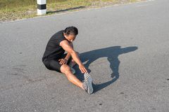I corridori maschii stanno allungando i muscoli della gamba per preparare per un funzionamento Fotografia Stock