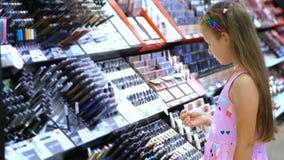 I cosmetici comperano, ragazza graziosa, bambino, con attenzione considera i prodotti cosmetici, nel deposito di bellezza Piccola video d archivio