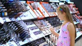 I cosmetici comperano, ragazza graziosa, bambino, con attenzione considera i prodotti cosmetici, nel deposito di bellezza Piccola archivi video