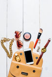 I cosmetici e gli accessori delle donne sono caduto dalla borsa beige su fondo bianco Fotografie Stock Libere da Diritti