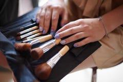 I cosmetici insaccano con l'insieme delle spazzole per trucco fotografia stock libera da diritti