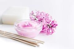 I cosmetici lilla con i fiori e la stazione termale hanno messo sul fondo bianco della tavola Immagine Stock