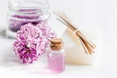 I cosmetici lilla con i fiori e la stazione termale hanno messo sul fondo bianco della tavola Fotografie Stock Libere da Diritti