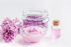I cosmetici lilla con i fiori e la stazione termale hanno messo sul fondo bianco della tavola Fotografie Stock