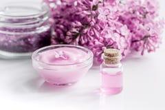 I cosmetici lilla con i fiori e la stazione termale hanno messo sul fondo bianco della tavola Fotografia Stock