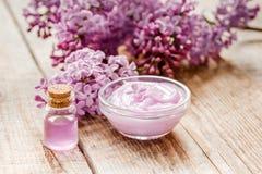 I cosmetici lilla con i fiori e la stazione termale hanno messo sul fondo di legno della tavola Fotografie Stock Libere da Diritti