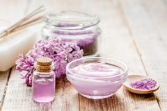 I cosmetici lilla con i fiori e la stazione termale hanno messo sul fondo di legno della tavola Fotografia Stock