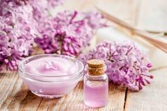 I cosmetici lilla con i fiori e la stazione termale hanno messo sul fondo di legno della tavola Immagine Stock Libera da Diritti