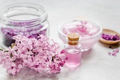 I cosmetici lilla con i fiori e la stazione termale hanno messo sul fondo di pietra della tavola Immagini Stock Libere da Diritti