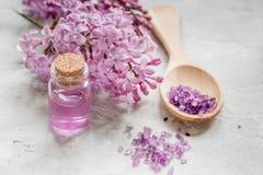 I cosmetici lilla con i fiori e la stazione termale hanno messo sul fondo di pietra della tavola Immagini Stock
