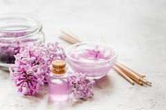 I cosmetici lilla con i fiori e la stazione termale hanno messo sul fondo di pietra della tavola Fotografia Stock Libera da Diritti