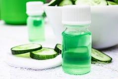 I cosmetici liquidi pelano la cura in una bottiglia ed in un cetriolo verde con una fetta di cetriolo su una tavola di legno bian fotografia stock libera da diritti