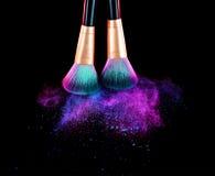 I cosmetici spazzolano e la polvere della polvere di trucco di esplosione fotografia stock