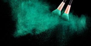 I cosmetici spazzolano e la polvere variopinta di trucco di esplosione sul nero immagini stock