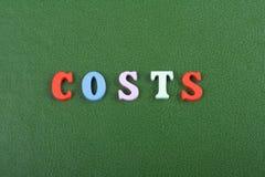 I costi esprimono su fondo verde composto dalle lettere di legno di ABC del blocchetto variopinto dell'alfabeto, copiano lo spazi Immagine Stock Libera da Diritti