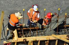 I costruttori versano il cemento ad un muro di cemento Immagini Stock Libere da Diritti